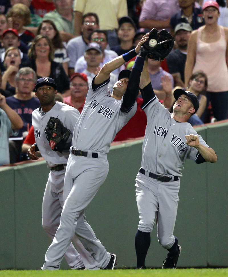 Yankees shortstop Derek Jeter catches a popup in front of third baseman Eduardo Nunez, left, and left fielder Brett Gardner. Nunez and Gardner both homered off Josh Beckett, but the Red Sox rallied for a 3-2 victory in 10 innings.