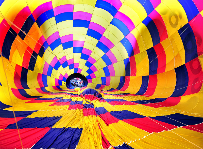 A hot air balloon owned and piloted by Andre Boucher of Derry, N.H., starts to inflate with air from high-powered fans at Railroad Park in Lewiston.