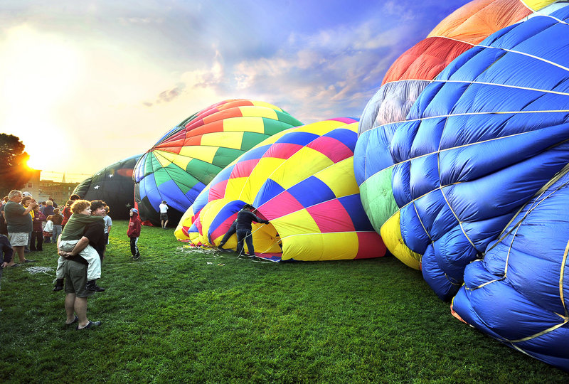 As the sun makes it way over the horizon, early-morning spectators watch hot air balloons being inflated by high-power fans at Railroad Park in Lewiston on Saturday. They will rise tall with blasts of hot air powered by propane burners.