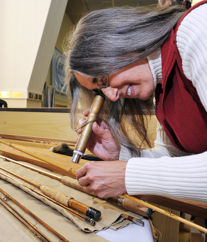 Kathy Scott uses a microscope to inspect the threads on a guide wrap on a bamboo rod. Fewer than 12 people in Maine are estimated to make bamboo rods for clients.