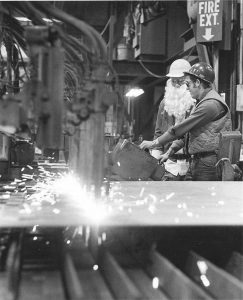 "In 1977, a reporter from The Times Record tagged along with Santa Claus as he made his rounds to various locales in the Mid-coast region during December. At Bath Iron Works' Harding Plant in East Brunswick, the jolly old elf ""traded in his pompoms for a hard hat"" and stopped for a consultation with Lewis Palmer, who showed St. Nick how to use a torch cutter. Palmer, whose son, Dwayne, is a longtime employee of The Times Record, died earlier this year. One more photo of Santa's 1977 Mid-coast exploits will appear in the Dec. 22 edition."