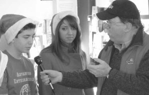 STUDENTS IN THE MORSE HIGH SCHOOL INTERACT CLUB speak with television personality Don Carrigan, right, from WCSH-TV Channel 6 at the Bath Train Station during the Coats for Kids collection on Saturday. The students are, from left, Kyle Wood-Nichols, president of the club, and Felicia Haggerthy, a member of the club and Miss Merrymeeting Bay.