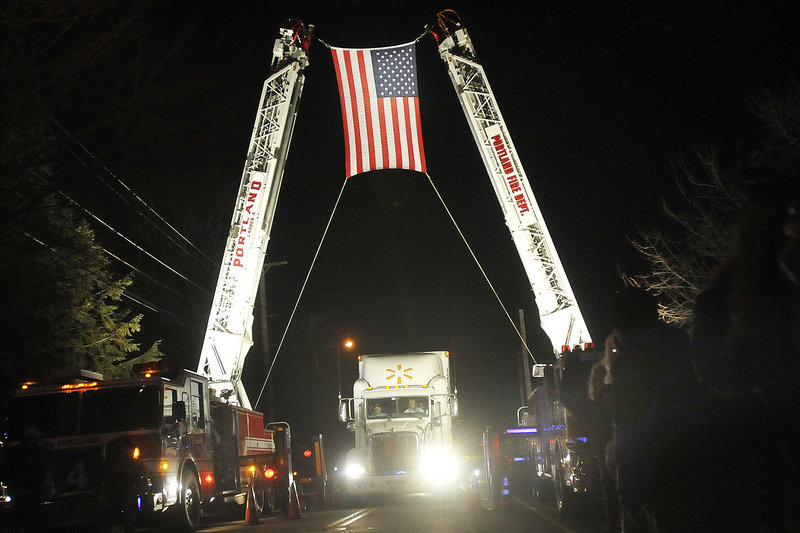 The convoy carrying wreaths from Harrington passes under an arch on Sunday outside Cheverus High School in Portland, where it stopped for a ceremony before continuing to Arlington National Ceremony. The wreaths will be laid on service members' graves.
