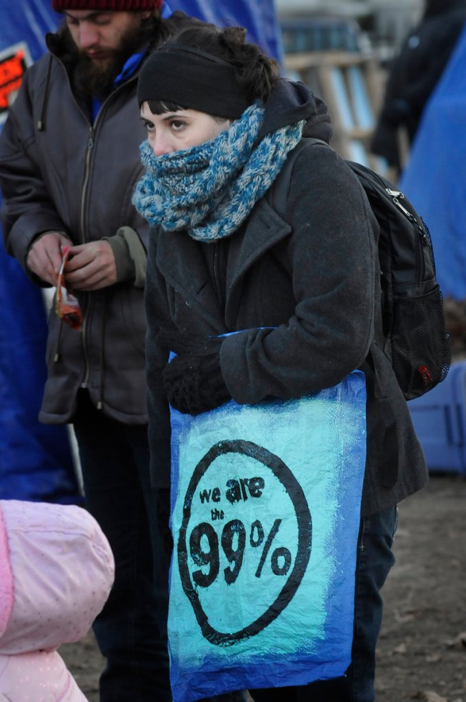 Erika Jordan of Auburn is bundled against the cold at an Occupy Maine meeting in Portland on Sunday. The group decided to file suit against the city to try to stay in Lincoln Park.