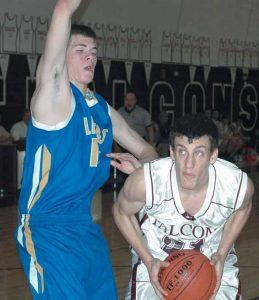 FREEPORT'S MITCH LOEMAN (21) looks to the basket while being defended by Lake Region's Alex Hartford during a boys high school Western Maine Conference game on Saturday at Freeport. The Falcons fell to 1-9 with a 63-55 setback.
