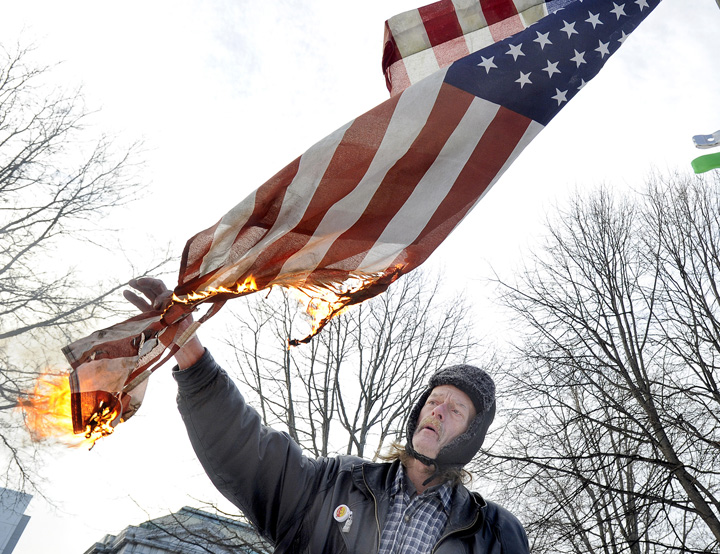 Occupy Maine member Harry Brown burns the camp flag as his way of properly disposing of it while other Occupy Maine protesters dismantled their tents in Portland's Lincoln Park this morning.