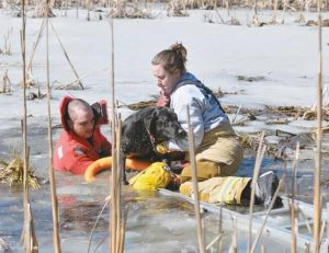 DURHAM FIRE AND RESCUE Capt. Mike Lacasse, left, and firefighter Kira Lacasse rescue a dog that had fallen through ice into a pond Friday. Firefighter Korey Enman Curtis, hidden from view, assisted.