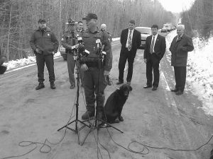 GAME WARDEN NORMAN LEWIS, with his dog, Clyde, answers questions at a news conference in Newburgh regarding finding the body of missing firefighter Jerry Perdomo of Seminole County, Fla. Perdomo had been missing since Feb. 16, and a man has been charged in connection with his death.