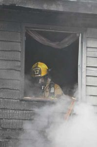 Durham Fire and Rescue Fire fighter Kira Lacasse works at overhauling the fire in a home at 21 Larrabee Lane today. (Photo courtesy of Michael Brillant)