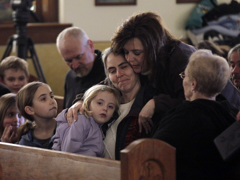Residents attending Mass at St. Francis Xavier Catholic Church hug before the start of services in Henryville, Ind., on Sunday. The church was in the path of a tornado that destroyed much of the town.