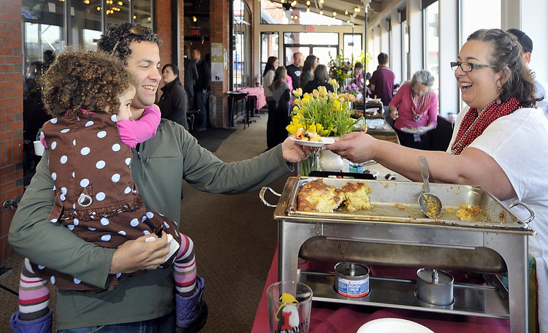 Andrew Tenenbaum of Portland, holding his daughter Harper, 3, gets a sample of the winning Creme Brulee French Toast served by Lisa Kostopoulos, owner of The Good Table restaurant in Cape Elizabeth, at the breakfast cook-off on Friday. She won by four votes.