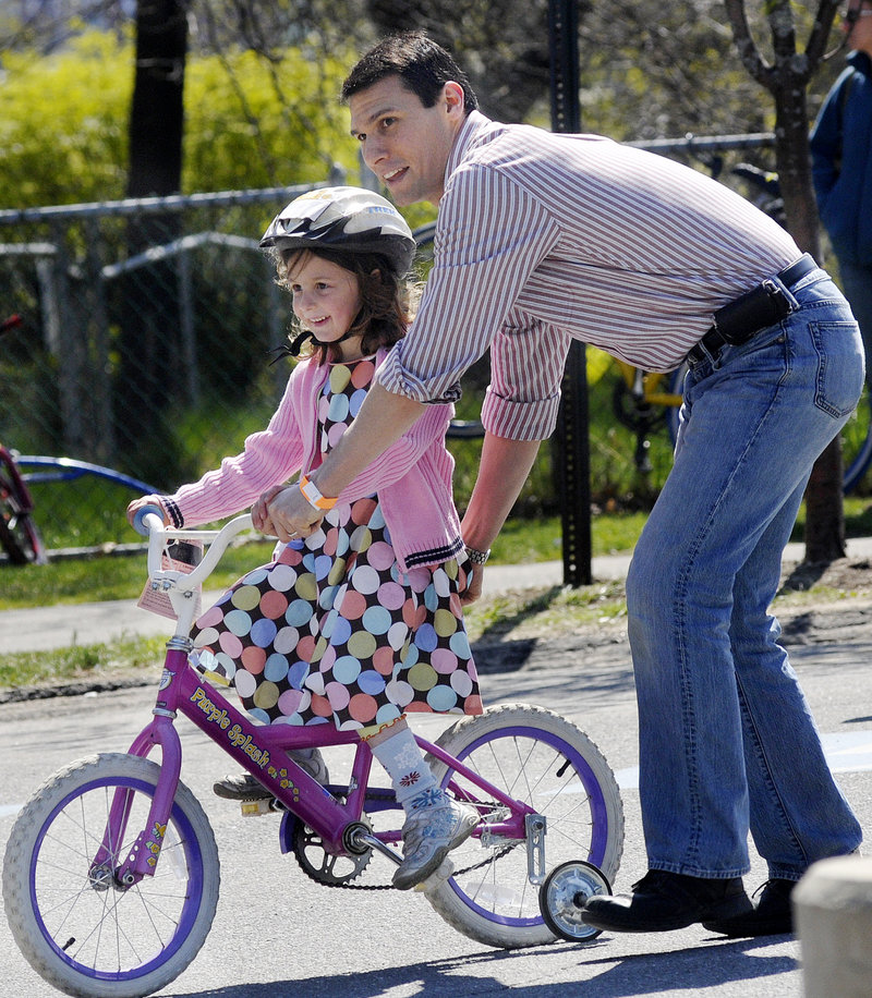 Sam Zager of Portland helps his daughter Maya, 5, as she tries out a bike. Members of the Bicycle Coalition of Maine were on hand at the swap to answer questions and offer advice.