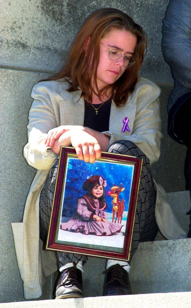 Logan Marr's mother, Christy Reposa, holds a photo of her daughter, who was asphyxiated when she was duct-taped to a highchair while in foster care. Logan's death launched reforms that began to trend toward removing fewer children from their families.