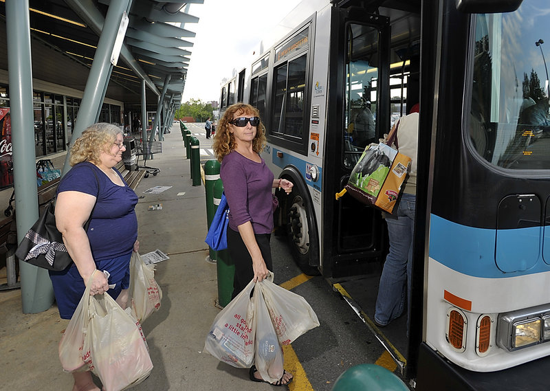Janet Burgess, a West End resident, boards a Metro bus at the Forest Avenue Hannaford supermarket. She says she misses the convenience of a car, but not the bills that came along with car ownership.