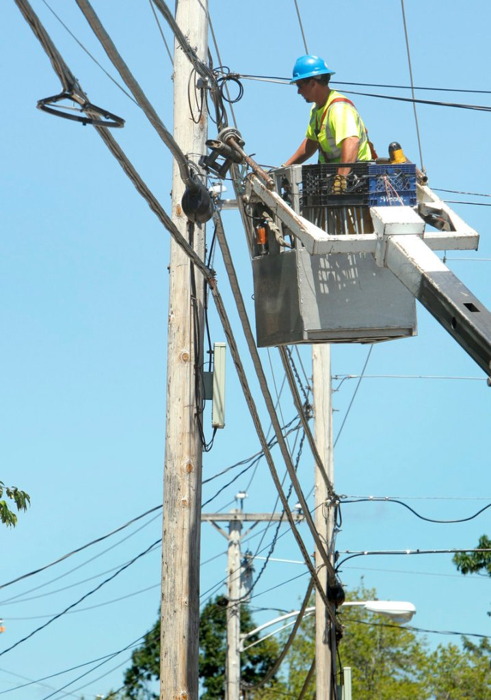 Ericson Estes of NextGen, a telecommunications company, works on a support line on Route 1 in Wells. The entirely above-ground network is strung along 29,000 utility poles.