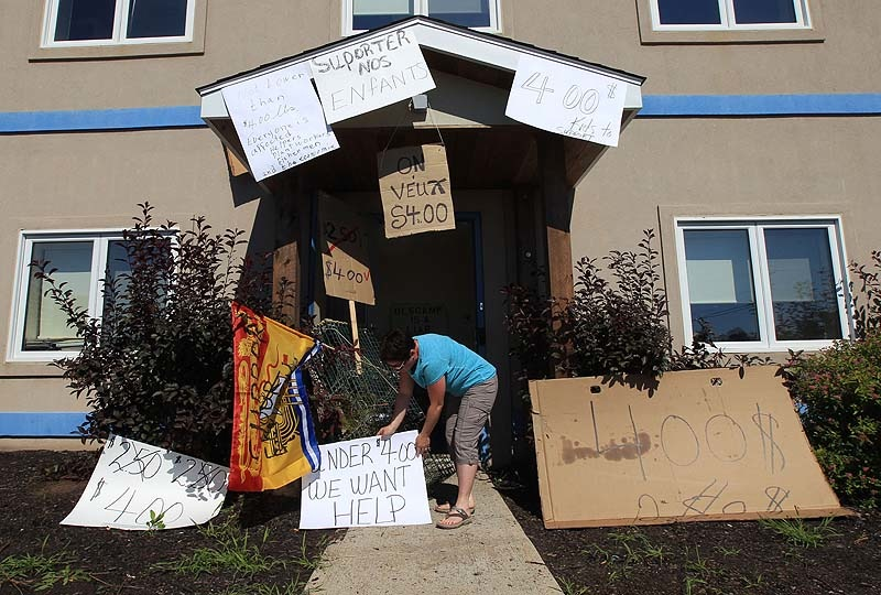 "Protesters put signs up around the entrance to Ashfield's office. One says, ""Under $4.00 – We Want Help."""