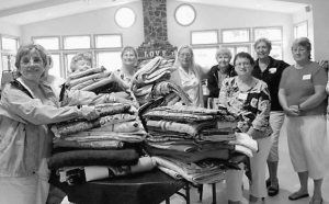 MEMBERS of the Ocean Waves Quilters sew labels on quilts for Camp Sunshine, Pictured from left are Phyllis Truesdell, Paula Paganucci, Mary Demond and Jan Wiehe. At right, the group delivers the quilts to Camp Sunshine. From left are Mary Ann Holcombe, Sally Weymouth, Shirley Freeman, Jan Oliver, Janet Kirkpatrick, Maryann Douglas, Donna Leith, Mary Demond and Nancy Hill.