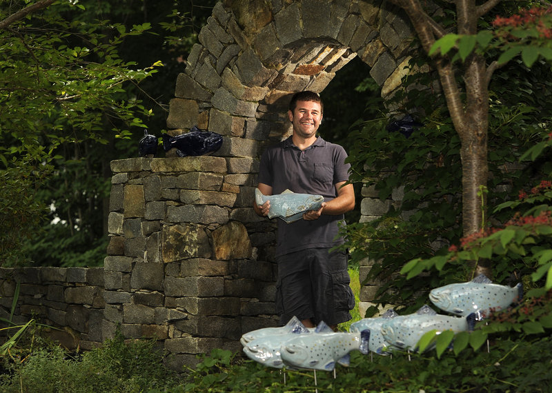 """Tyson Weiss' Falmouth yard holds some of his ceramic fish, which """"swim"""" through the greenery, providing a fluid aesthetic."""