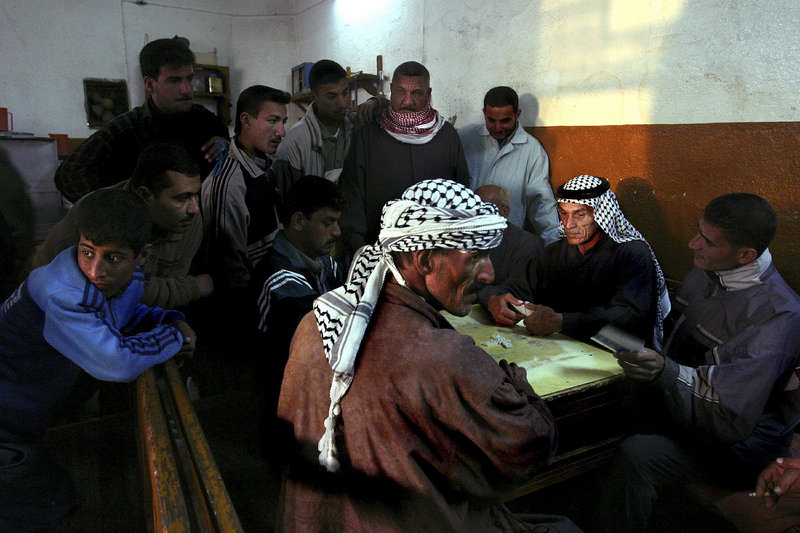 Iraqis play dominoes, a popular evening pastime, in Amara, Iraq, October 2003