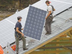 BRANDON BERNARD, left, and Joe Maisonave carry one of 44 photovoltaic solar collection panels toward its place in a solar array on the roof of Reversing Falls Lobster Wharf in Harpswell. Each panel weighs about 44 pounds and can harness 240 watts of energy.