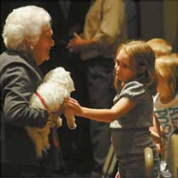 BARBARA BUSH and her dog Mini-Me are greeted by Brewer Community School students after she and Maine first lady Ann LePage visited the school on Monday. See story, page A5.