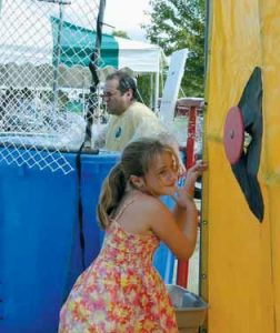 KARA BRIAND, 7, took three earnest shots at the target at the dunk tank on Saturday, and gets the OK to push the button, dunking Steve Balboni, a member of the town's fire department, who was willing to take the plunge first in a series of local, business owners, officials, state represenatives and more -- all to raise money for a skatepark. Jasper Merriman, 10, of Little Compton, R.I., at right, competes in his first-ever lobster crate races , and soon became adept at running across the floating span of wet, slippery crates.