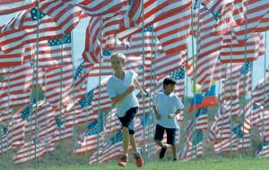 CHILDREN run among flags, below, flying at Pepperdine University , in Malibu, Calif. The flag display is in honor of the victims of the Sept. 11, 2001, attacks against the U.S. One flag from the nationality of each person killed that day was erected.