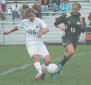 BRUNSWICK MIDFIELDER Libby Arford (26) passes ahead with Oxford Hills defender Bryanne Starbird (15) close by during a KVAC girls high school soccer game in Brunswick on Tuesday. The undefeated Dragons won 5-1.