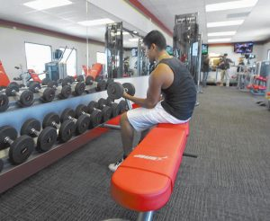 A CUSTOMER, above, works out at a Snap Fitness truck stop gym in Dallas. Gym manager Rick Limitone, below, demonstrates a work out machine.