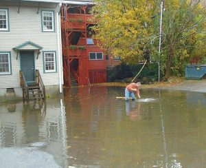 CURT FISH wades into knee-high water with a rake to unclog a sewer drain behind the Sharon Drake Real Estate office on Water Street in Bath, where heavy rains from Hurricane Sandy flooded the basement.