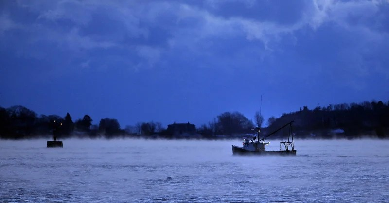 A groundfishing vessel glides out into Casco Bay before dawn on Jan. 23 as arctic sea smoke rises from the water.