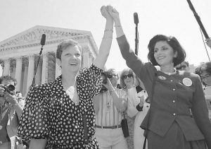 IN THIS APRIL 26, 1989, file photo, Norma McCorvey, Jane Roe in the 1973 court case, left, and her attorney Gloria Allred hold hands as they leave the Supreme Court building in Washington after sitting in while the court listened to arguments in a Missouri abortion case. Months later, the high court ultimately upheld the Missouri law in the case, Webster v. Reproductive Health Service, which placed restrictions on public employees and facilities when it came to abortions. In 1995, McCorvey shocked abortion advocates by announcing that she now opposes the procedure.