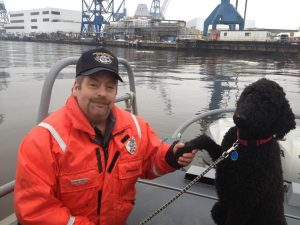 PHOTO COURTESY PAUL WHITE/BIWCpl. Harland Stanley shakes hands with Hoku after he and fellow Bath Iron Works security officer Sgt. Paul White rescued the dog Saturday morning.