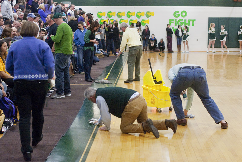 Paul Pendleton, left, vice principal of McAuley High, and athletic director Joseph Kilmartin unsuccessfully try to dry the floor during one of the interruptions of the game between McAuley and Deering.