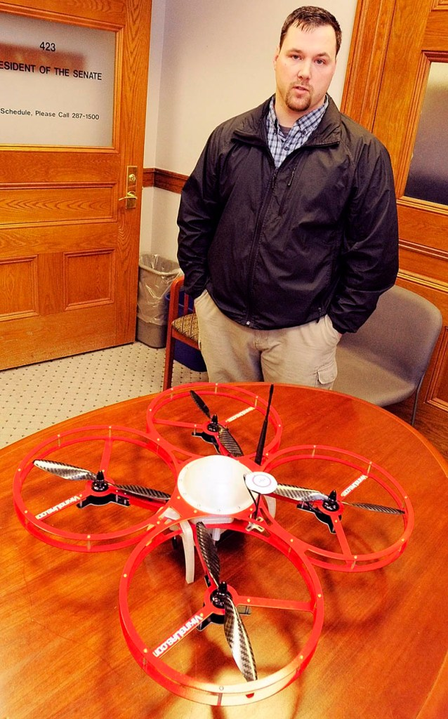 """(FILE) Christopher Taylor, president and drone designer for Viking Unmanned Aerial Systems of Limington, talks about his company's FR-Xtreme model that is on table Tuesday February 26, 2013 at the State House in Augusta. The company's website calls it a """"Vertical Take-Off and Landing Commercial Quad Copter built to serve multiple industries. """""""
