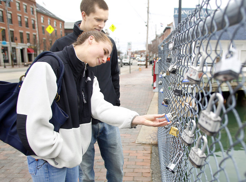 Sarah Rengold and her boyfriend Erik Born from Virginia read messages written on padlocks hung on a waterfront fence in Portland. Love locks also appear on bridges and fences in Paris, Moscow, New York City and elsewhere.