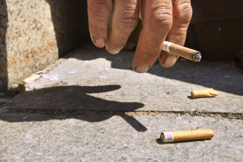 A Monument Square smoker flips his ashes on the ground near some illegally disposed cigarette butts. A Monument Square business owner is trying to institute a program that pays 5 cents per cigarette butt to keep the square clean.