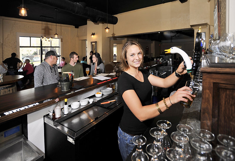 Lily Sund, a bartender at Little Tap House in Portland, draws a draft as, at the bar, Portlanders Bob Cole, left, Kyle Chapin and Ashley Lafreniere visit.