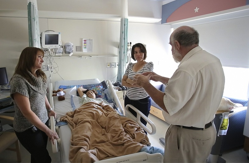 In this September 2012 file photo, interpreter George Bentley talks to Rina Yadira Galan with instructions and advice from Nurse Practioner Nicole Mizner, at left, before a young patient is discharged from Maine Medical Center in Portland. The cost of free care provided by Maine hospitals to uninsured patients has more than doubled since 2007, and those expenses will continue to grow unless Maine Medicaid expansion becomes law, hospital officials said.