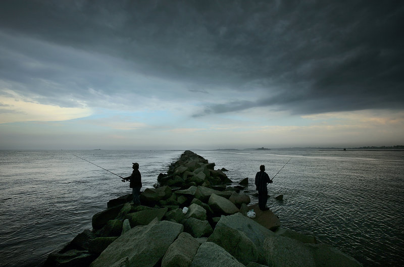 With a storm front moving in overhead, two anglers fish from the jetty at Camp Ellis. The 6,600-foot jetty, with the ocean on the left side and the mouth of the Saco River on the right, is a popular location for striper fishing. Over many decades, it also has been the primary cause of severe erosion requiring a costly fix.