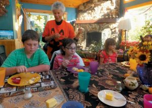 CAROL EMERSON, volunteer leader for The Amazing PES Kids' Garden, watches students eat locally produced foods recently at EdgeWater Farm Bed & Breakfast in Phippsburg. The students are members of The Amazing PES Kid's Garden, which will host a school garden open house from 10 a.m. to 3 p.m. Saturday. A similar open garden will take place in Bath.