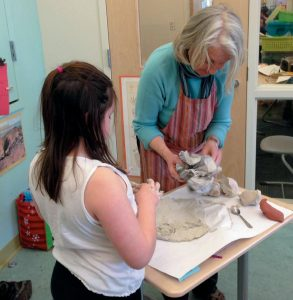 SQUIDGE DAVIS, artist-in-residence at Harriet Beecher Stowe Elementary School in Brunswick, works with clay and first graders.