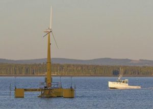 A LOBSTER BOAT passes the country's first floating wind turbine off the coast of Castine last week. The University of Maine's 9,000-pound prototype has been generating power since the summer.