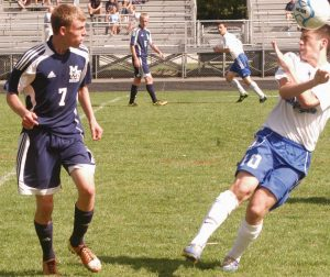 MT. ARARAT HIGH SCHOOL'S Isaac Bradshaw (10) heads the ball away from Mt. Blue's Sam Taylor during KVAC boys soccer action Saturday in Topsham.