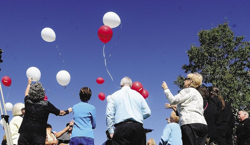 People watch a balloon release after the groundbreaking ceremony for the Parents of Murdered Children Maine chapter's new monument Sunday in Augusta.