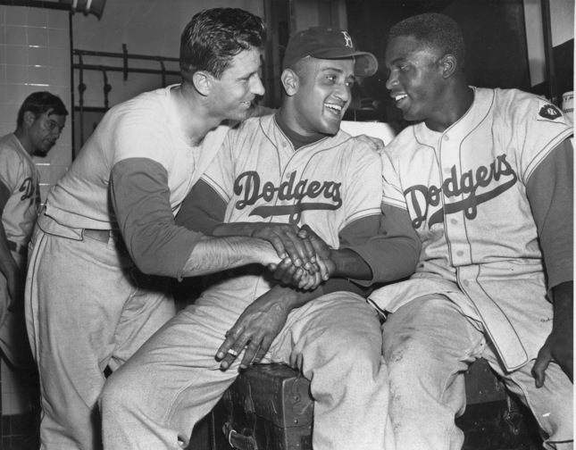 """Brooklyn Dodgers baseball player Andy Pafko, left, Don Newcomb, center, and Jackie Robinson shake hands in their dressing room after the Dodgers beat the Philadelphia Phillies 5-0, in New York. That flowing blue """"Dodgers"""" script across the front of the jersey that followed them from Brooklyn."""