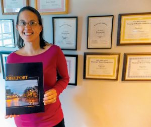 CAROLINE PELLETIER, assistant to the town planner, shows off the award-winning Freeport town report.