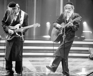 IN THIS PHOTO taken Oct. 22, Ultra-Orthodox Jewish singers Arie Gat, right, and his brother Gil, perform as they participate in an Israeli TV show in Neve Ilan, Jerusalem. For most Israelis, the common perception of the ultra-Orthodox Jewish minority is that of an insulated, segregated society devoted to studying ancient biblical texts and rejecting the ills of secular life. But the pair of devout, soft-spoken brothers in skullcaps and sidecurls are now breaking down some stereotypes by emerging as the most unlikely of media darlings — reality rock stars.