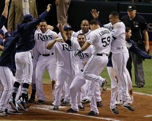 TAMPA BAY RAYS' Jose Lobaton (59) is surrounded by teammates as he heads to home plate after hitting a walk off home run in the ninth inning against the Boston Red Sox in Game 3 of an American League baseball division series in St. Petersburg, Fla., on Monday. Tampa Bay won the game, 5-4.
