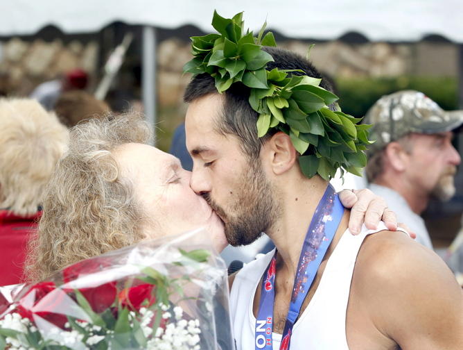 Photos by Tim Greenway/Staff Photographer Rob Gomez of Saco receives a congratulations kiss from his mother Connie after winning the Maine Marathon Sunday in a time of 2 hours, 24 minutes and 21 seconds in Portland on October 6, 2013.